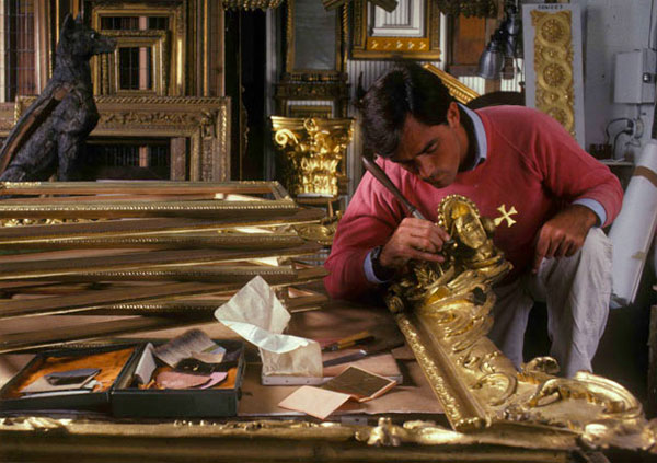 William Adair applying gold leaf to a frame.